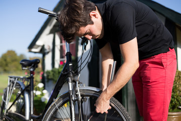 Man preparing bicycle to go on a cycling trip