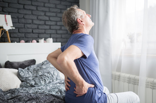 Senior man with lower back pain siting on bed