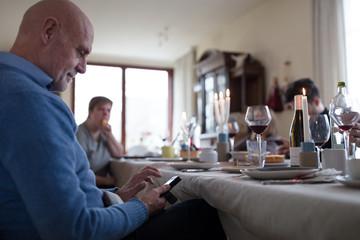 Senior man using mobile phone during family dinner
