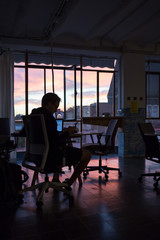 Silhouette of man working late in office at dusk