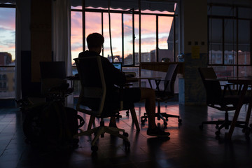 Man sitting on chair working late in office at dusk