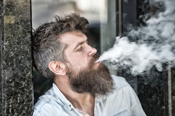 Man with beard and mustache smoking, black marble background. Smoking and habits concept. Hipster with tousled hair and gray on relaxed indifferent face with white smoke flying out of mouth.
