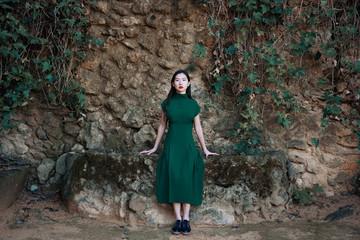 Portrait of woman leaning on rocky wall