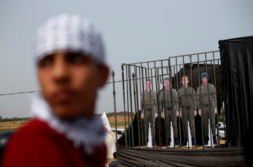 A protester stands next to dummies depicting Israeli soldiers during a protest at the Israel-Gaza border where Palestinians demand the right to return to their homeland, east of Gaza City