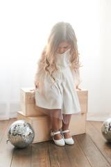 Children's fashion. Little stylish girl in white dress.