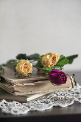 Still life with dry roses on vintage lace fabric and old book