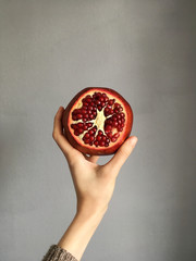 Woman's hand holding a pomegranate