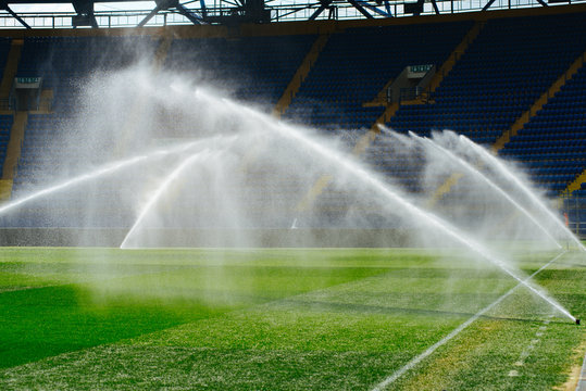 Irrigation turf. Sprinkler watering football field. System working on fresh green grass on football or soccer stadium.