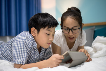 Female and boy playing on tablet, smiling, laying on bed.
