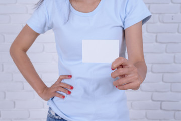 Young businesswoman holding blank white business card.
