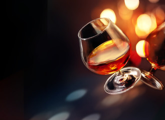Cognac wineglass with colorful festive lighting on black background