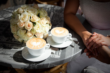 Two cups of coffee with a heart pattern. Couple in love sit in cozy street cafe with wedding flowers on table. Bride and groom are holding hands.