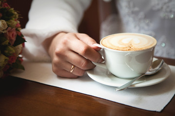 Bride holds cup of coffee with a heart pattern in cozy cafe. Woman has weddin ring.