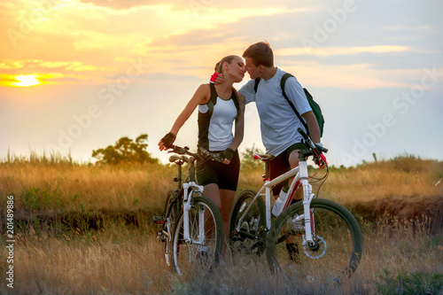 Beautiful Young Couple In Love With Bicycles At Sunset Stock Photo