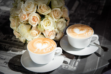 Two cups of coffee with a heart pattern for couple in love are in cozy street cafe with wedding roses flowers on table.