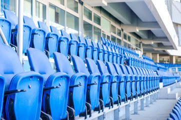Fotorollo Stadion Sitting fans colored plastic chairs at the football stadium background. Empty stadium football field green grass for soccer athletics arena.