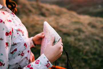 Stylish traveler woman with hat holding map on top of mountains, emotional happy moment, travel concept, space for text. Girl  walking along the grass at the top of the mountain in sunset