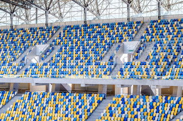 Sitting fans colored plastic chairs at the football stadium background. Empty stadium football field green grass for soccer athletics arena.