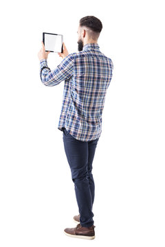 Side back view of young business bearded man holding pad tablet computer taking photo. Blank screen. Full body isolated on white background.