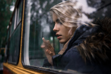melancholy cute girl draws a finger on the bus window