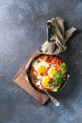 Traditional Israeli Cuisine dishes Shakshuka. Fried egg with vegetables tomatoes and paprika in cast-iron pan on wooden board with cloth and herbs over blue texture background. Top view, space.