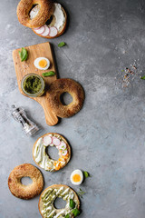 Variety of homemade bagels with sesame seeds, cream cheese, pesto sauce, eggs, radish, herbs served on crumpled paper with ingredients above over grey texture background. Top view, copy space.