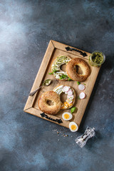 Variety of homemade bagels with sesame seeds, cream cheese, pesto sauce, eggs, radish, herbs served on wooden tray with ingredients above over blue texture background. Top view, space.