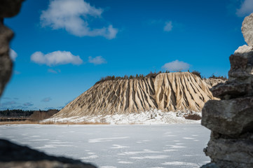 Slope of an abandoned slag heap covered ravines against the blue sky. Winter landscape. Frozen lake. Rummu, Estonia.