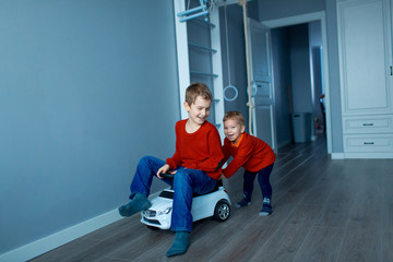 Two happy children riding on baby car in room, indoors.