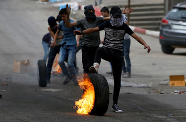 Palestinian protester rolls a burning tire during clashes with Israeli troops in Hebron, in the occupied West Bank