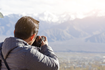 photographer taking landscape photo of himalayas mountain hill
