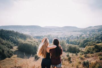 Beautiful young girls walk on autumn mountain slopes, fun, jump. female friendship