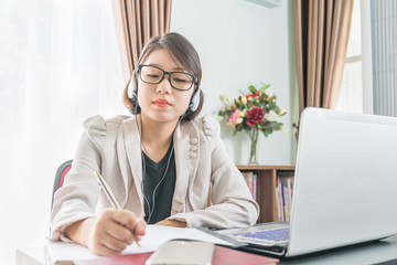 Teenage girl working on laptop in home office