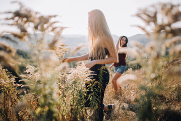 Beautiful young girls walk on autumn mountain slopes, fun, jump. female friendship