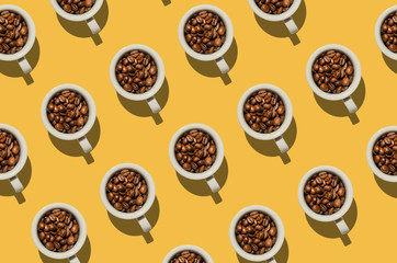 Pattern. Cup with coffee beans concept. Group of white cups on yellow background. Creative style.