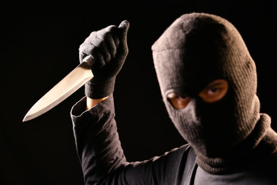 The robber hold the knife in hand on black background
