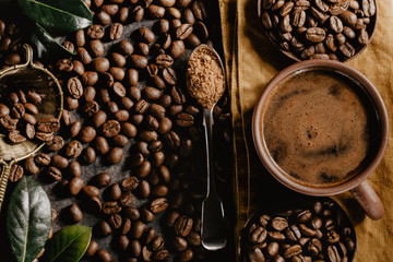 Cup of brewed coffee among aromatic beans