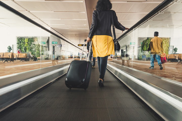 Young girl traveler walking with carrying hold suitcase in the airport.