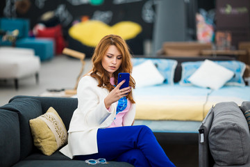 Young woman calling with cell telephone while sitting alone in furniture store, attractive female having talking conversation with mobile phone while rest on sofa.