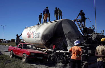 Locals loot cement from an AfriSam cement truck during protests in Mahikeng
