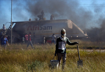 A local carries a bucket and a spade, after looting cement from an AfriSam cement truck during protests in Mahikeng