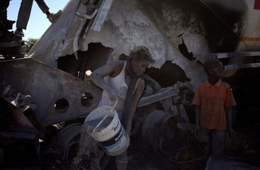 A local loots cement from an AfriSam cement truck during protests in Mahikeng