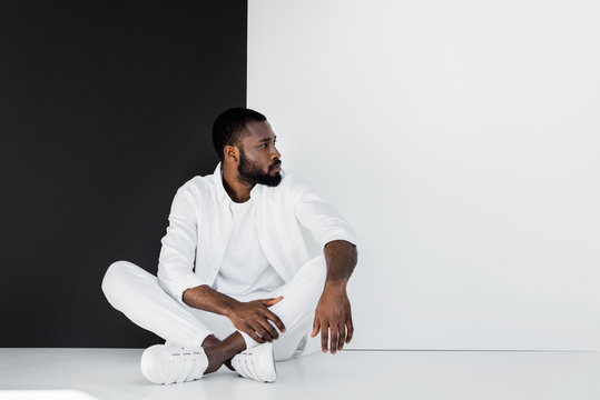 handsome stylish african american man sitting on floor near black and white wall and looking away