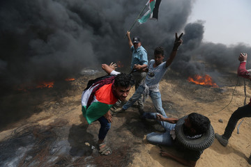 Demonstrators take cover during clashes with Israeli troops at a protest where Palestinians demand the right to return to their homeland, at the Israel-Gaza border in the southern Gaza Strip