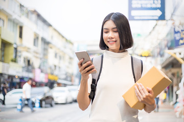 Portrait of happy delivery asian woman her hands holding cardboard box and mobile phone street walk outdoors, young asian woman carry brown box delivery service smartphone technology concept