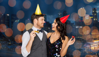 birthday, celebration and holidays concept - happy couple with party blowers and caps having fun over singapore city night lights background