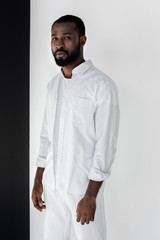 handsome african american man in white stylish clothes looking at camera