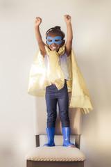 Little girl wearing yellow superhero cape