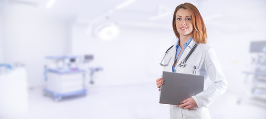 Portrait of a beautiful woman doctor with tablet over blue clinic interior