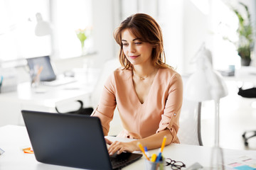 business, technology and people concept - businesswoman with laptop computer working at office
